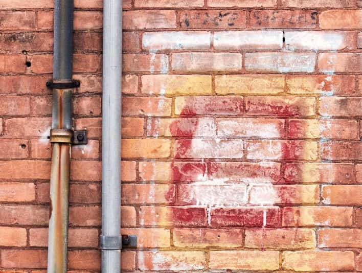 Stipplr Stock Photo Red Brick Wall With Spray Painted Graffiti and Steel Pipes