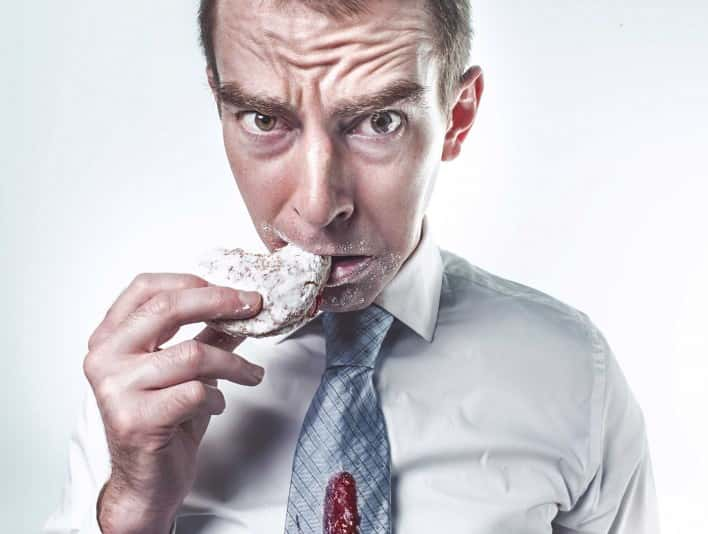 Stipplr Stock Photo Male Office Worker Spills Jelly While Biting into Sugar Powdered Donut