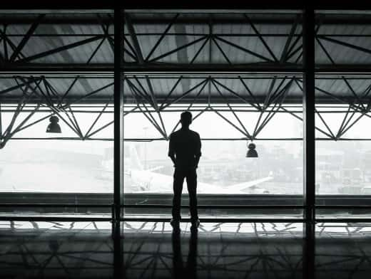Stipplr Stock Photo Man Stands Inside Airport Terminal Staring At Plane Parked At Gate