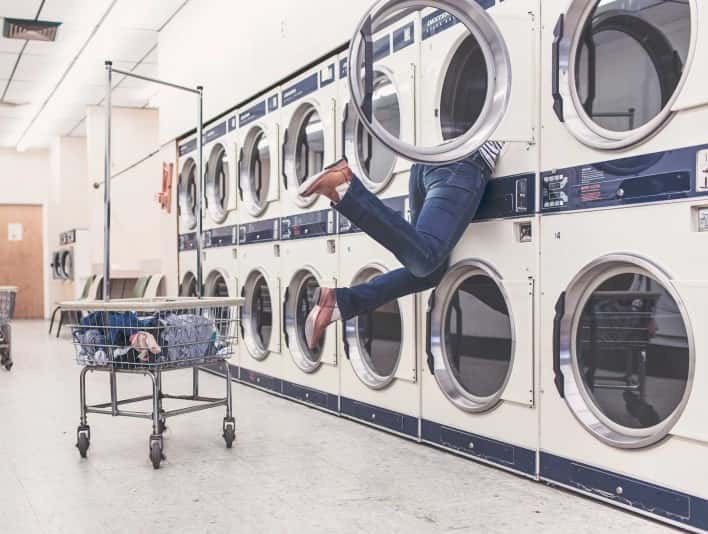 Stipplr Stock Photo Woman Halfway Into Laundry Machine Searching For Lost Sock